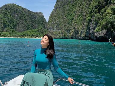 Menikmati segarnya udara di alam saat di atas kapal yang sedang menuju pulau Phiphi yang berada di Thailand. Bermain di pantai serasa bukan masalah bagi Karenina dan tidak takut hitam. (Liputan6.com/IG/karenina_sunny)