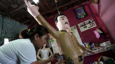 "Seorang pekerja menempelkan pistol mainan ke boneka raja narkoba Joaquin ""El Chapo"" Guzman saat menyelesaikannya di Reynosa, Meksiko (21/7/2015). Guzman melarikan diri dari penjara melalui terowongan yang ia buat pada bulan lalu. (REUTERS/Daniel Becerril)"