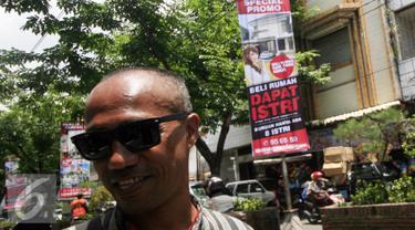 Seorang juru parkir mengatur kendaraan dengan latar belakang benner ilklan beli rumah dapat istri di kawasan Nonongan, Solo (3/2/2016). Iklan di pasang untuk menarik minat calon pembeli. (Liputan6.com/Boy Harjanto)