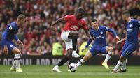 Gelandang Manchester United, Paul Pogba (tengah) menggiring bola dari kawalan pemain Chelsea pada pertandingan Liga Inggris di Old Trafford (11/8/2019). MU menang telak 4-0 atas Chelsea. (AFP Photo/Oli Scarff)