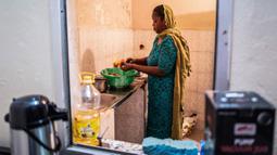 Ngone, saudara ipar Bara Tambedou, memasak makanan berbuka puasa pada bulan suci Ramadan, di Dakar, Senegal, 25 April 2020. Tahun ini, banyak keluarga menjalankan Ramadan di rumah dengan larangan pertemuan publik dan penerapan jam malam untuk menekan penyebaran Covid-19. (AP/Sylvain Cherkaoui)