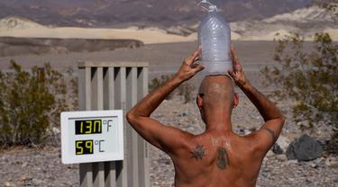 Steve Krofchik mendinginkan kepalanya dengan botol berisi es batu di Taman Nasional Death Valley, California, Amerika Serikat, Senin (17/8/2020). Temperatur udara tertinggi di Dunia -- 54,4 derajat Celcius -- tercatat di Taman Nasional Death Valley pada Minggu 16 Agustus. (AP Photo/John Locher)