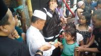 Jeritan dan desak-desakan mewarnai proses bagi-bagi uang pengusaha Makassar di pertengahan Ramadan yang sedang hujan saat itu. (Liputan6.com/Eka Hakim)
