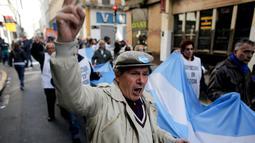 Sekelompok pensiunan berbaris sambil memegang bendera Argentina menuju Plaza de Mayo, Buenos Aires, Argentina, Selasa (22/8).  Mereka terdiri dari para pekerja dan pensiunan yang melawan kebijakan ekonomi Presiden Mauricio Macri. (Victor R. Caivano/AP)