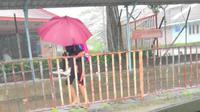 Anak perempuan gendong teman sekolahnya yang autis saat hujan. (dok. screenshot video Facebook @autisme.malaysia)