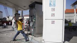 Pengunjuk mencoba menghancurkan tangki pom bensin saat demo pemilu di Port-au-Prince, Haiti (18/1). Warga menuduh pemilu presiden Haiti berjalan curang yang menyebabkan kemarahan warga hingga membakar fasilitas umum. (REUTERS/Andres Martinez Casares)