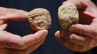 Seorang arkeolog menunjukkan pecahan keramik berupa stempel bertuliskan huruf Ibrani kuno yang ditemukan di sebuah situs penggalian di Yerusalem (22/7/2020). Tim arkeolog Israel menemukan pusat penyimpanan administratif berusia 2.700 tahun di Yerusalem. (Xinhua/Gil Cohen Magen)