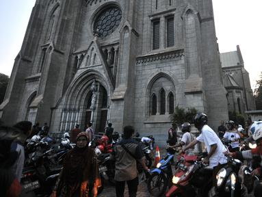 Umat muslim yang akan menunaikan salat Idul Adha di Masjid Istiqlal memasuki halaman Gereja Katedral, Jakarta, Minggu (11/8/2019). Gereja Katedral menyediakan lahan parkir bagi jemaah Masjid Istiqlal yang akan melaksanakan salat Idul Adha sebagai bentuk toleransi. (merdeka.com/Iqbal S Nugroho)