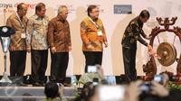 Presiden Jokowi memukul gong sebagai tanda pembukaan acara Indonesia Infrastructure Week (IIW) di Jakarta Convention Center, Rabu (9/11). Acara ini dihadiri oleh 22.000 peserta dan menghadirkan 350 proyek. (Liputan6.com/Faizal Fanani)