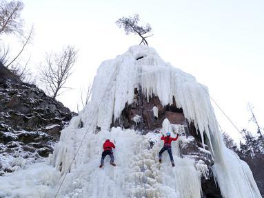 Orang-orang memanjat dinding es buatan di desa Vir, Republik Ceko, Minggu (14/2/2021). Ketika suhu turun di Republik Ceko, pemanjat tebing memanfaatkan kondisi beku dengan mengubah permukaan batu menjadi dinding es setinggi 20 meter untuk pendaki. (AP Photo/Petr David Josek)