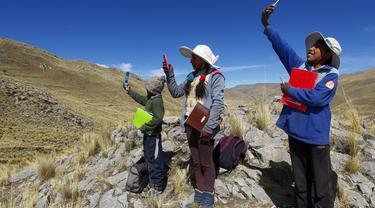 """Cabrera bersaudara mencari sinyal di atas bukit untuk menghadiri kelas virtual di komunitas dataran tinggi Conaviri yang terpencil di Andes Peru, 24 Juli 2020. Sejak sekolah ditutup akibat COVID-19, mereka bergantung pada ponsel untuk mengakses platform """"Belajar di Rumah"""".  (Carlos MAMANI/AFP)"""