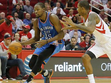 Pemain Oklahoma City Thunder Kevin Durant (kiri) membawa bola dijaga ketat pemain Houston Rockets Trevor Ariza saat pertandingan NBA di Toyota Center, Amerika Serikat, (2/11/2015). Rockets menang 110 - 105 atas Thunder. (Reuters/ Thomas B. Shea)