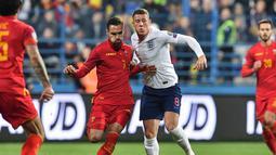 Duel antara Ross Barkley dengan Marko Vesovic pada laga kedua Kualifikasi Piala Eropa 2020 yang berlangsung di Stadion Pod Goricom, Podgrica, Selasa (26/3). Timnas Inggris menang 5-1 atas Montenegro. (AFP/Andrej Isakovic)