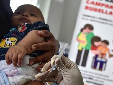 Petugas menyuntikan Vaksin Campak dan Rubella (MR) kepada bayi saat dilakukan imunisasi di sebuah puskesmas, Banda Aceh, Rabu (19/9). Pemprov Aceh akhirnya membolehkan pelaksanaan vaksinasi MR yang mengandung enzim babi. (CHAIDEER MAHYUDDIN / AFP)