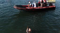 Seorang perenang memegang sebuah salib kayu yang dilemparkan ke laut saat restu upacara air menandai hari Epiphany Orthodox, di pelabuhan Thessaloniki, Yunani utara, (6/1). (AFP Photo/Sakis Mitrolidis)