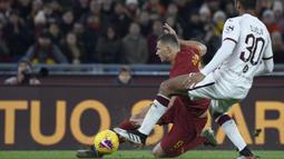 Striker AS Roma, Edin Dzeko, dijatuhkan bek Torino, Koffi Djidji, pada laga Serie A Italia di Stadion Olimpico, Roma, Minggu (5/12). Roma kalah 0-2 dari Torino. (AFP/Filippo Monteforte)