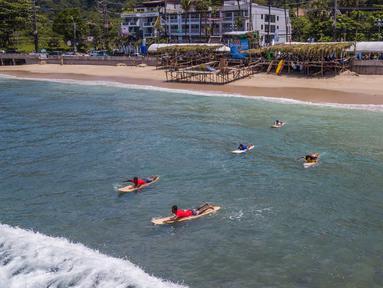 Para peserta berenang menuju area perlombaan dalam Kontes Selancar Phuket 2020 di Pantai Kalim di Phuket, Thailand (14/9/2020). Acara yang berlangsung selama tiga hari itu merupakan bagian dari kampanye pemerintah Thailand untuk mempromosikan pariwisata dan merangsang perekonomian. (Xinhua/Zhang Ker