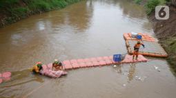 Pekerja Dinas Kebersihan mengangkat sampah kasur di Kali Pesanggrahan, Jakarta Selatan, Rabu (4/11/2020). Sampah-sampah yang terbawa arus air terjaring di penyaringan sampah yang dipasang untuk mengantisipasi penyumbatan pada musim penghujan bisa terjadi banjir. (merdeka.com/Dwi Narwoko)