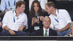 Pangeran Harry, Kate Middleton dan Pangeran William ketika menyaksikan pertandingan renang, di Tollcross International Swimming Centre, Skotlandia, Senin (28/7/14). (REUTERS/Phil Noble)