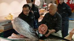 Pedagang Yamayuki memisahkan kepala dan ekor ikan tuna sirip biru seberat 405 kilogram pada lelang tuna di pasar ikan Tsukji, (5/1). Lelang ikan dengan harga mencapai miliaran rupiah ini rutin digelar setiap awal tahun. (AP Photo / Eugene Hoshiko)