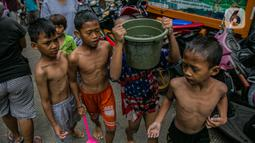 Anak-anak korban banjir bermain di luar Gedung Sekolah SDN 01/02 Kampung Melayu, Jakarta, Selasa (9/2/2021). Gedung sekolah tersebut menjadi salah satu posko pengungsian bagi Sebagian korban banjir di kawasan Kebon Pala. (Liputan6.com/Faizal Fanani)
