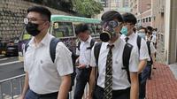 Para siswa sekolah mengenakan topeng dan helm berjalan di luar St. Paul's College selama protes di Hong Kong, Selasa (3/9/2019). Puluhan ribu siswa di Hong Kong mogok sekolah di hari pertama tahun ajaran baru. (AP Photo/Kin Cheung)