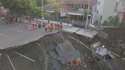 Petugas pemadam kebakaran memeriksa kondisi tanah amblas di Jalan Raya Gubeng, Surabaya, Rabu (19/12). Salah satu akses utama di Kota Surabaya itu amblas diduga karena proyek pembangunan gedung di sekitar lokasi (Liputan6.com/Pool/FB Dishub Kota Surabaya)