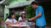 Petugas Kelompok Penyelenggara Pemungutan Suara (KPPS)  berseragam Sekolah Dasar memberikan pelayanan kepada warga yang menggunakan hak pilih pada Pilkada DKI 2017 di TPS 45 Kelurahan Kebon Pala, Jakarta, Rabu (15/2). (Liputan6.com/Gempur M Surya)