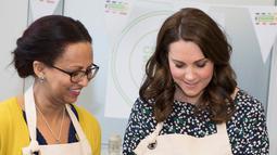 Kate Middleton bersama rekannya mempersiapkan masakan untuk acara Commonwealth Big Lunch di Luke's Community Centre, London, Inggris (22/3). Big Lunch merupakan acara tahunan terbesar di Inggris. (Paul Edwards/ Pool via AP)