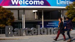 Orang-orang berjalan melewati poster yang mengumumkan Mobile World Congress (MWC) 2020 di lokasi pameran di Barcelona, Spanyol, Selasa (11/2/2020). Pembatalan MWC 2020 dilakukan setelah diadakannya pertemuan darurat oleh para petinggi penyelenggara. (AP Photo/Emilio Morenatti)