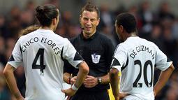 Wasit Mark Clattenburg memperingatkan Pemain Swansea City Chico Flores (kiri) dan Jonathan de Guzman (Kanan) Pada pertandingan Liga Premier Inggris antara Swansea City dan Arsenal di Stadion Liberty di Swansea (28/09/13). (AFP/Paul Ellis)