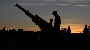 Tentara Yordania menyiapkan meriam penanda waktu berbuka puasa di Benteng Amman pada 19 Mei 2019.  Di Yordania dan beberapa negara timur tengah, tembakan meriam saat matahari terbenam menandai akhir dari puasa selama bulan suci Ramadan. (REUTERS/Muhammad Hamed)