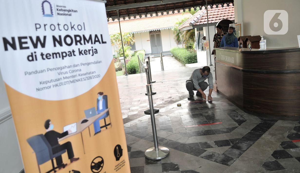 Petugas memasang tanda jaga jarak untuk antrean pengunjung di pintu masuk Museum Kebangkitan Nasional, Jakarta, Senin (8/6/2020). Pengelola menyiapkan standar protokol kesehatan jelang dibuka kembali untuk umum saat masa PSBB Transisi guna memutus penyebaran Covid-19. (merdeka.com/Iqbal S Nugroho)