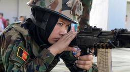 Seorang kadet perempuan Afghanistan melakukan latihan menembak sasaran di Chennai, Rabu (19/12). Sembilan belas kadet tentara Afghanistan perempuan mengambil bagian dalam program pelatihan militer India. (ARUN SANKAR / AFP)