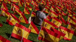 Seorang perempuan duduk di antara bendera Spanyol untuk mengenang korban COVID-19 di Madrid, Minggu (27/9/2020). Asosiasi keluarga korban virus corona memasang 53.000 bendera kecil Spanyol di sebuah taman Madrid untuk menghormati mereka yang meninggal akibat pandemi. (AP Photo/Manu Fernandez)