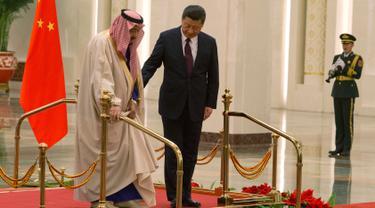 Presiden China Xi Jinping membantu Raja Arab Saudi Salman bin Abdulaziz al-Saud berjalan saat mengikuti upacara penyambutan di Beijing, China (16/3). (AP Photo / Ng Han Guan)