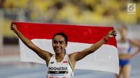 Pelari Indonesia Triyaningsih membawa bendera merah putih setelah mencapai garis finis dalam cabang olahraga atletik nomor lari 10 km putri SEA Games 2017 di Stadion Nasional Bukit Jalil, Malaysia, Kamis (24/8). (Liputan6.com/Faizal Fanani)