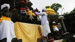 Pemangku Pura sedang merapikan Padmasana untuk upacara upacara Mecaru dalam perayaan hari Raya Nyepi Nyepi dan Tahun baru Saka 1941 di Pura Tribhuana Agung Sukmajaya Depok, Jawa Barat, Selasa (5/3). (Liputan6.com/Herman Zakharia)