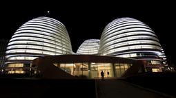 Seorang pengunjung saat berjalan didepan gedung Galaxy Soho yang baru dibuka rancangan arsitek Irak - Inggris Zaha Hadid di Beijing 27 Oktober 2012. (REUTERS / Jason Lee)
