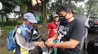 Pentolan VIking Persib Club Yana Umar membagikan masker dan sembako kepada warga di Bandung. (Bola.com/Erwin Snaz)
