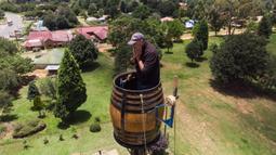 Pandangan aerial Vernon Kruger berada dalam tong di atas tiang dengan ketinggian 25 meter di Dullstroom, 16 Januari 2020. Kruger ingin tinggal di dalam tong selama 64 hari untuk pecahkan rekor yang dipegang dirinya pada 1997 dengan tinggal di dalam tong selama 54 hari. (ANTOINE DEMAISON/AFP)