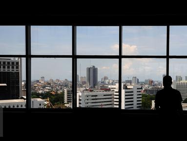 Seseorang mengamati kota Jakarta dari dalam Gedung Mina Bahari IV KPP, Rabu (26/10). Berdasar data CTBUH, pada 2015 lalu Jakarta menjadi kota yang paling banyak memiliki gedung setinggi 200 meter dengan jumlah 7 gedung. (Liputan6.com/Helmi Fithriansyah)