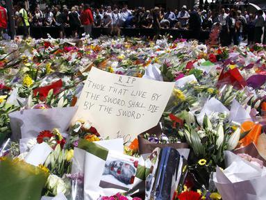 Sejumlah orang berdiri di balik pembatas tumpukan bunga di dekat Kafe Lindt, Sidney, Australia (16/12/2014). (REUTERS/David Gray)