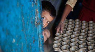 Seorang anak melihat keluar pintu ketika pengrajin tembikar membawa lampu minyak yang terbuat dari tanah liat untuk dikeringkan menjelang festival Diwali di Prayagraj, India, Kamis (17/10/2019).  Diwali merupakan festival lampu yang penting bagi umat Hindu di seluruh dunia. (AP/Rajesh Kumar Singh)