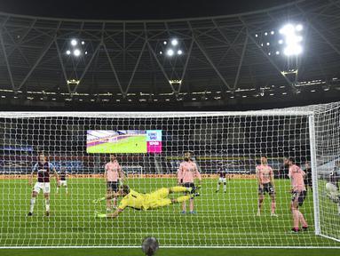 Pemain West Ham United Issa Diop (kanan) mencetak gol ke gawang Sheffield United pada pertandingan Liga Inggris di London Stadium, London, Inggris, Senin (15/2/2021). West Ham United menang 3-0. (Glyn Kirk/Pool via AP)