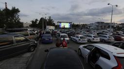 Suporter menyaksikan pertandingan Viktoria Plzen dan Sparta Praha di sebuah bioskop drive-in di Pilsen, Republik Ceko, Rabu (27/5/2020). Di tengah pandemi COVID-19, suporter Ceko dapat menyaksikan pertandingan bola lewat layar di bioskop drive-in. (AP Photo/Petr David Josek)