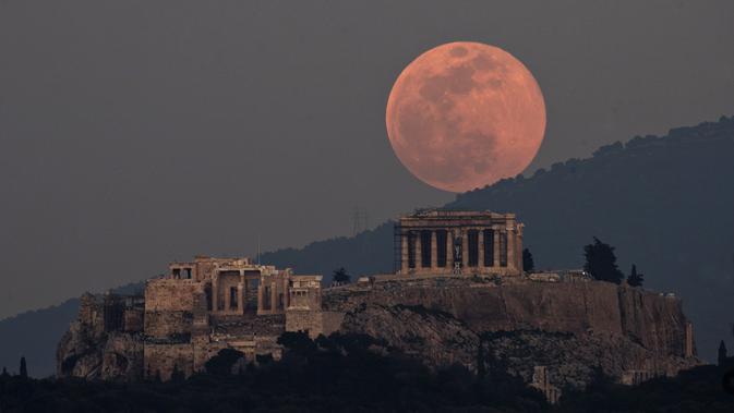 Bulan naik di atas Parthenon di Bukit Acropolis kuno di Athena, Yunani, pada 19 Februari 2019. (Petros Giannakouris/AP)