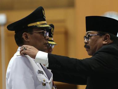 Gubernur Jawa Timur Soekarwo (kanan) melantik Bupati Tulungagung terpilih hasil Pilkada 2018, Syahri Mulyo di Jakarta, Selasa (25/9). Syahri saat ini sudah berstatus tahanan KPK. (Merdeka.com/Imam Buhori)