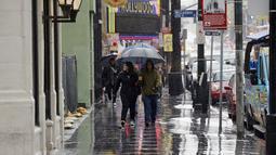 Wisatawan memakai payung sambil berjalan di trotoar Hollywood Walk of Fame di California, Rabu (6/1/2016). Badai El Nino melanda wilayah selatan California dengan membawa hujan deras ke kawasan yang sempat dilanda kekeringan. (REUTERS/Kevork Djansezian)