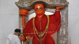 Seorang pendeta berdoa di hadapan patung Dewa Hanuman di Prayagraj, India, Senin (8/6/2020). India kembali membuka tempat ibadah, pusat perbelanjaan, dan restoran setelah tiga bulan lockdown karena pandemi virus corona COVID-19. (AP Photo/Rajesh Kumar Singh)